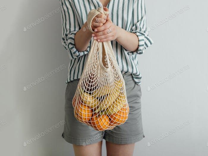 Frau stehend mit Netzbeutel in den Händen