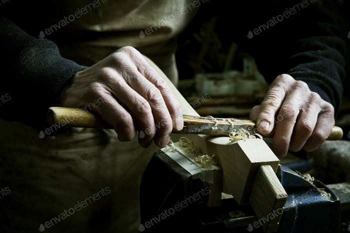 A man working in a furniture maker's workshop, using a rasp on a piece of wood in a clamp.