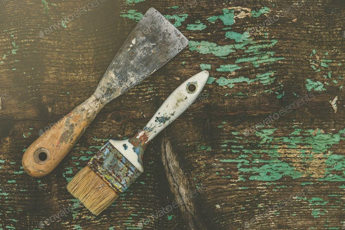 Old paintbrush and spatula on rustic wooden board