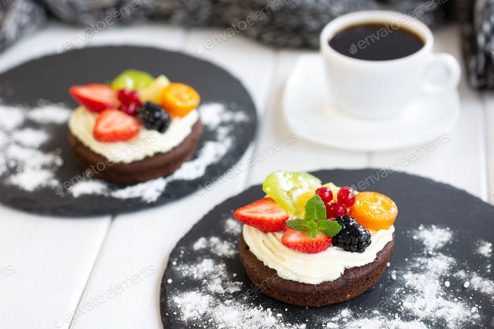 Chocolate cupcakes with cream cheese, fruits and berries. Coffee dessert