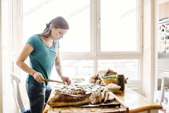 Young woman preparing open faced sandwiches in brightly lit home