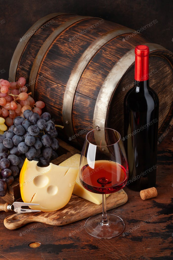 Wine bottle, grapes, cheese and glass of red wine