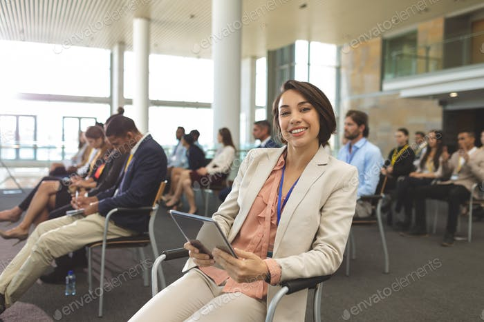 Businesswoman with digital tablet looking at camera during seminar in office building