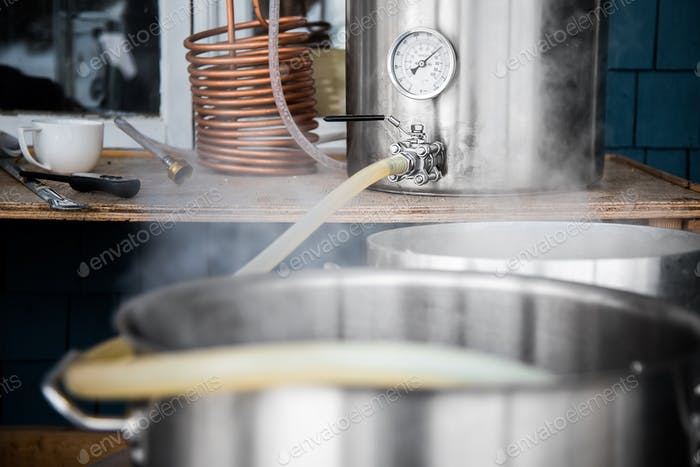 Home Brewing Kit and Pouring Craft Beer Wort into the Boil Kettl