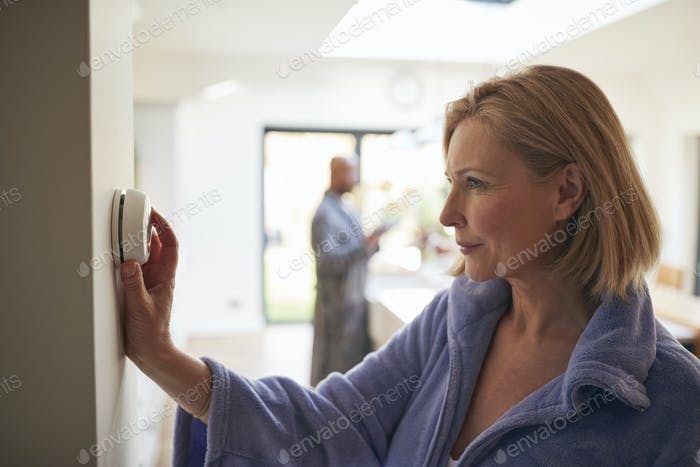 Mature Woman Turning Control Dial On Digital Central Heating Thermostat At Home