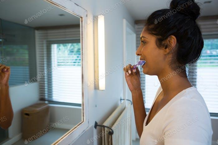 Woman brushing teeth at home