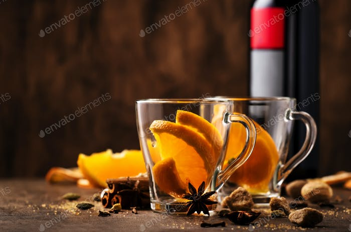Hot mulled red wine with spices and fruits preparing