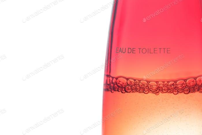 Bubbles in a flask of eau de toilette on a white background