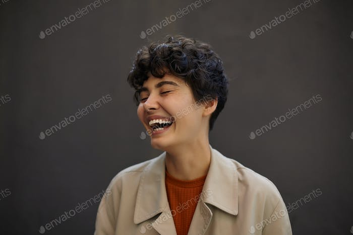 Close-up of attractive happy young dark haired female with short haircut laughing happily