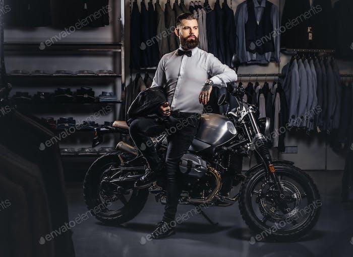Элегантно одетый татуированный мужчина позирует рядом с ретро спортивный мотоцикл в магазине мужской одежды