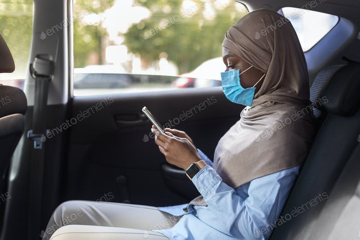 Black muslim businesswoman in hijab wearing medical mask on backseat of car