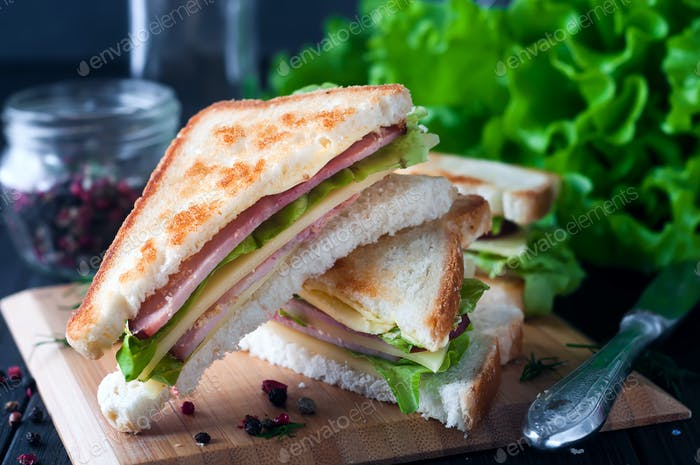 Club sandwich with a salad on a wooden plate