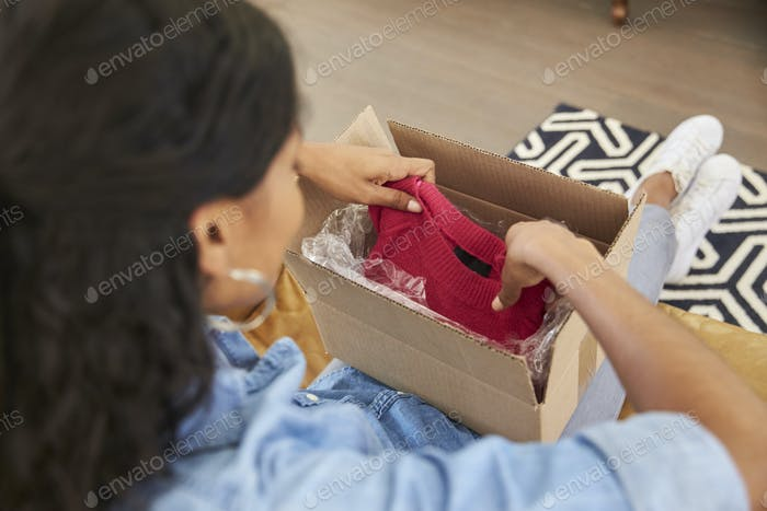Woman Sitting On Sofa At Home Opening Online Clothing Purchase