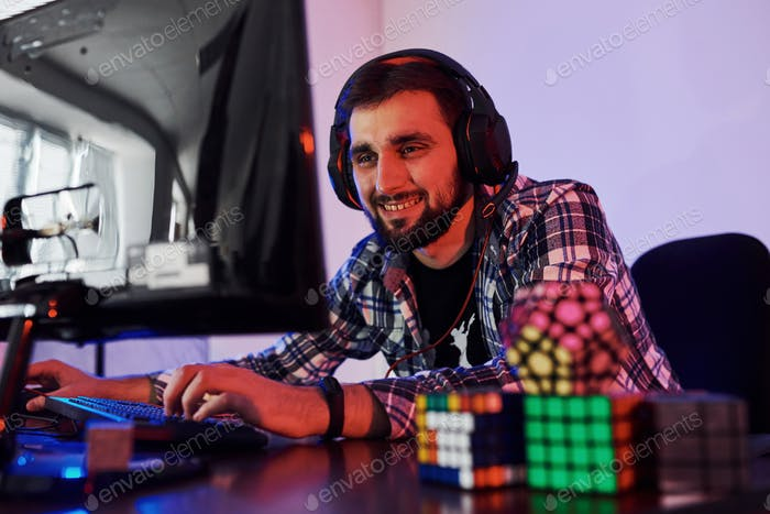Smiling during the process. Portrait of young bearded pro gamer playing in online video game