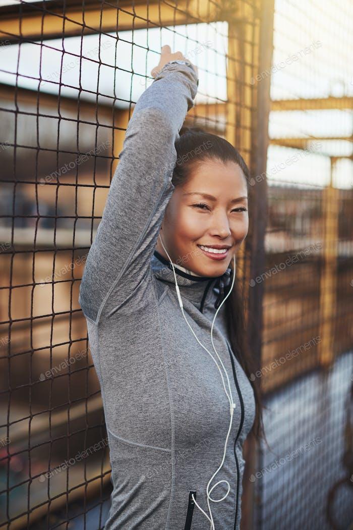 Asiatische Frau in Sportbekleidung lehnte sich gegen eine Netzwand im Freien
