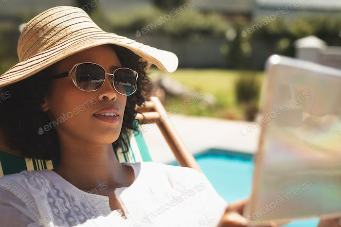 Woman with hat and sunglasses using digital tablet in her backyard on a sunny day