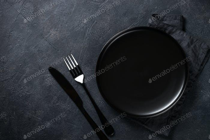 Schwarzer Teller, Besteck und Serviette auf Steintisch Draufsicht