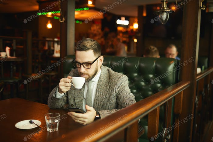Businessman with phone in cafe