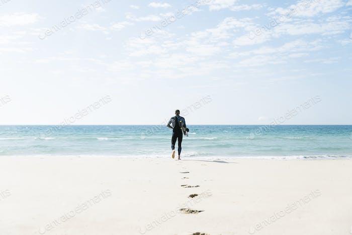 Hübscher Mann Kitesurfer läuft.