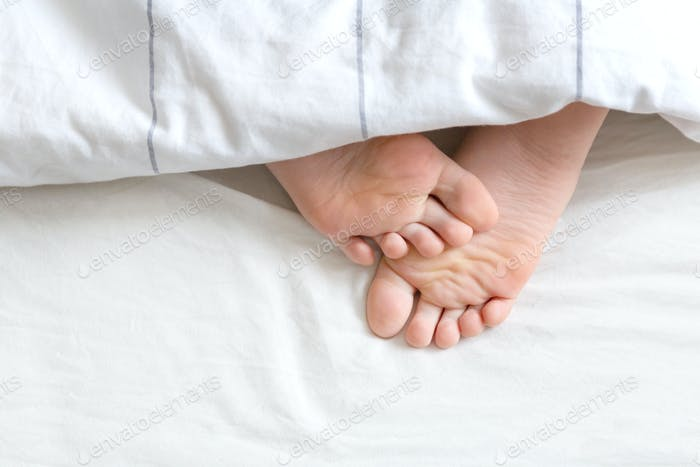 Bare feet under the bedding