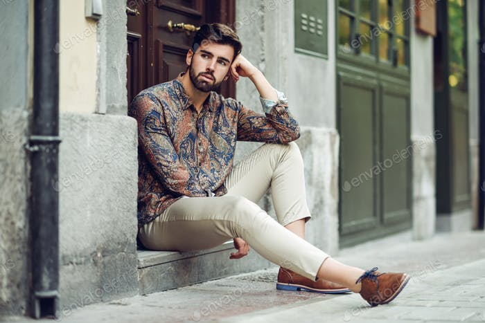Young bearded man, model of fashion, sitting in an urban step we