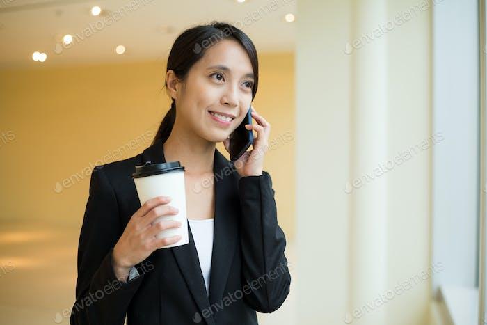 Empresaria asiática hablar con el teléfono móvil y hablar con el teléfono móvil