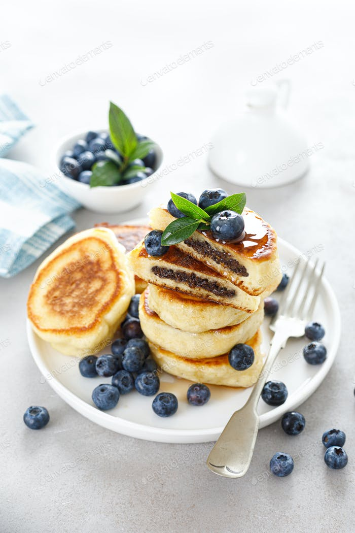 Fluffy souffle pancakes with chocolate filling and fresh blueberry for breakfast