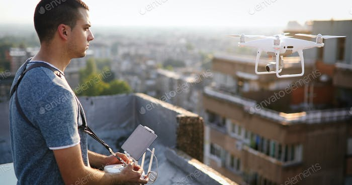 Man with drone flying at the city on rooftop