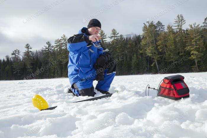 Hombre pesca en hielo en un lago del norte de Minnesota en una soleada mañana de invierno