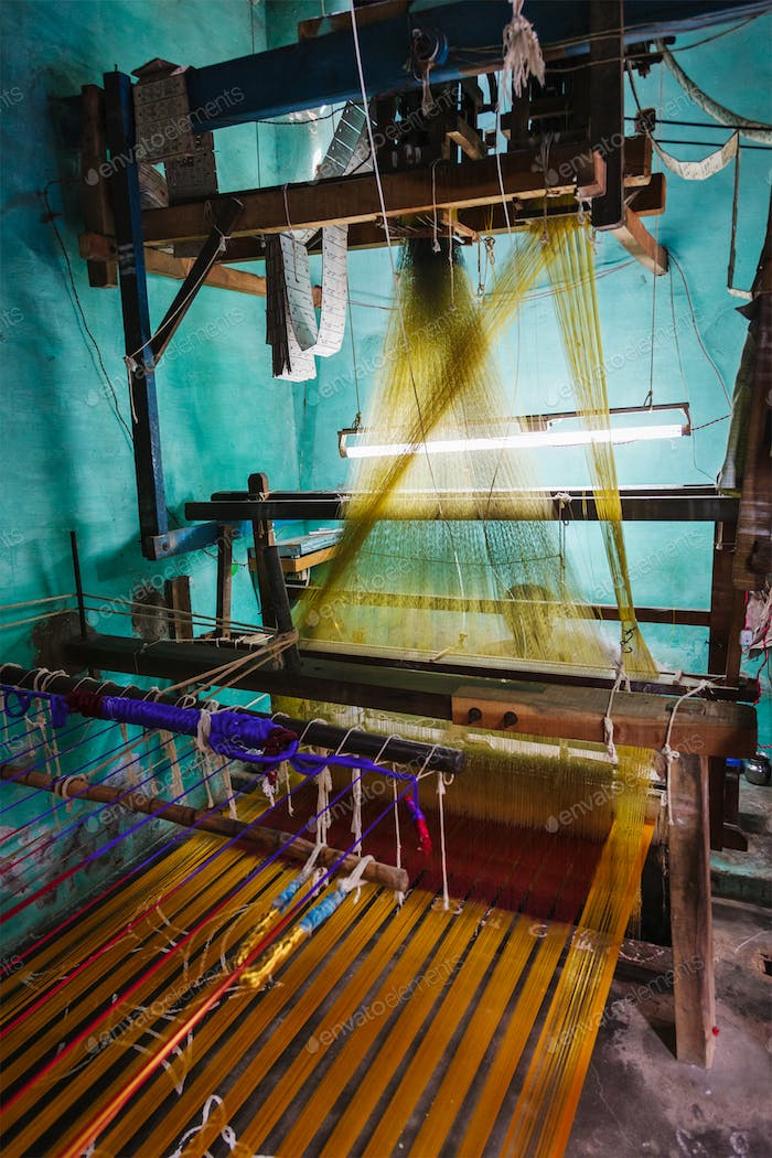 Man weaving silk sari on loom in India