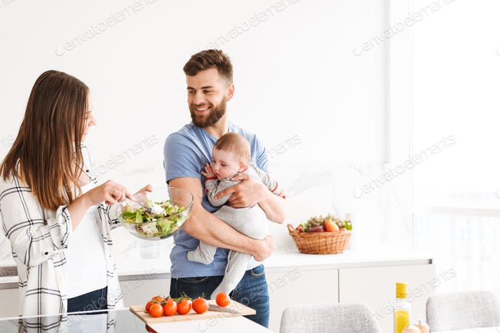 Happy parents with their baby son cooking in kitchen.