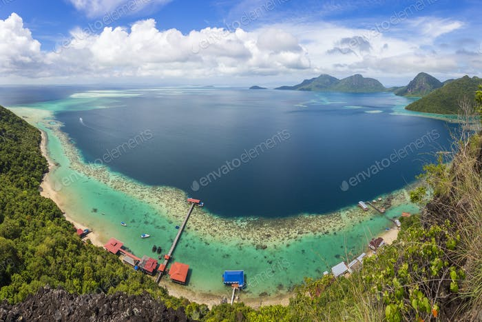 Wide angle view along coastline of tropical island, mountains in the distance.