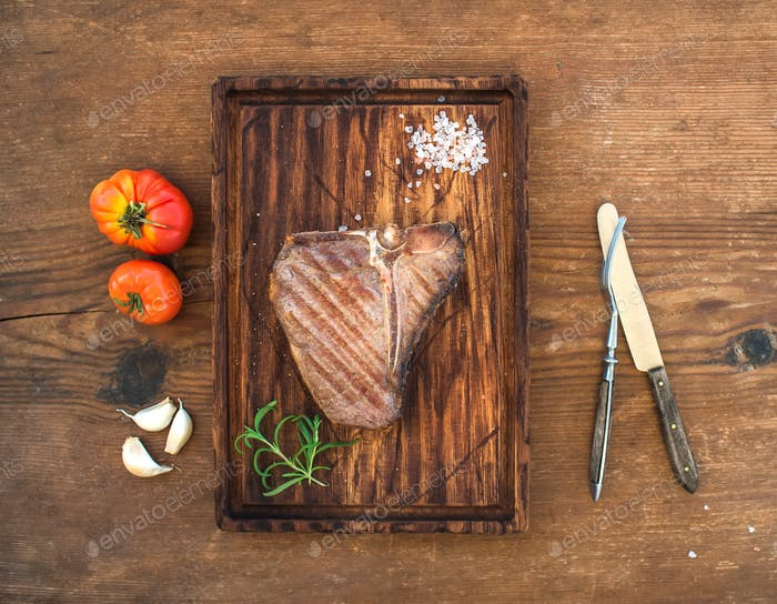 Cooked meat t-bone steak on serving board with garlic cloves, tomatoes, rosemary and spices