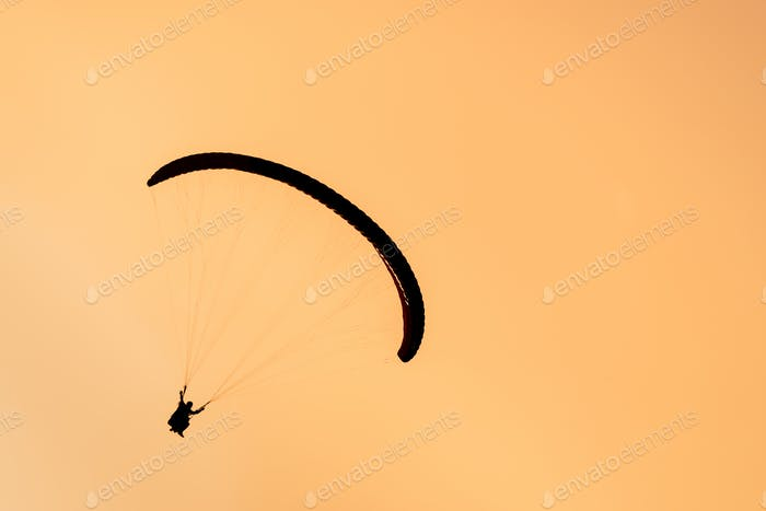 Silhouette of paraglider tandem flying in orange sky