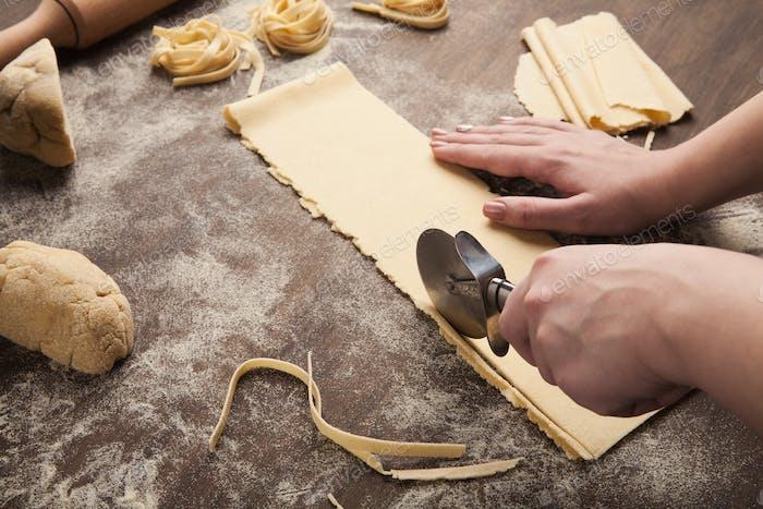 Küchenchef mit Radschneider in der Zubereitung von Pasta