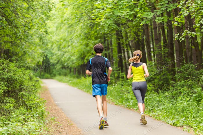 fitness, sport, friendship and lifestyle concept - smiling couple running outdoors.