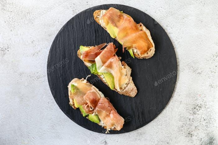 Bruschetta with prosciutto and cream cheese. Bread with hamon and cream cheese.