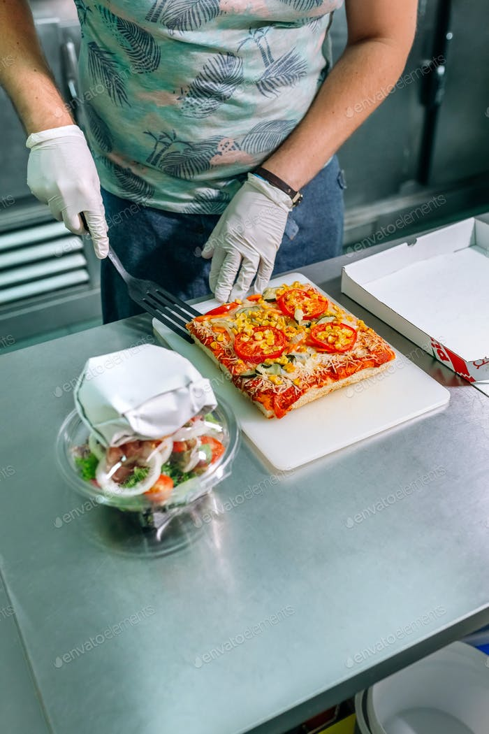 Unrecognizable cook preparing pizza to takeaway