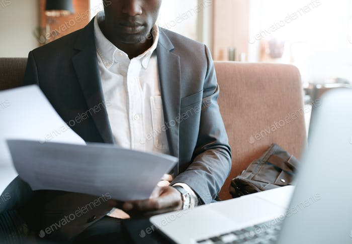 Businessman going through some documents at cafe