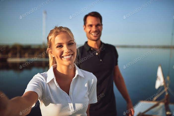 Junges Paar lächelnd beim Zusammenstehen auf ihrer Yacht