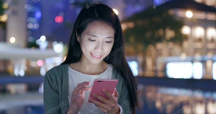 Frau sendet SMS auf Handy in der Nacht