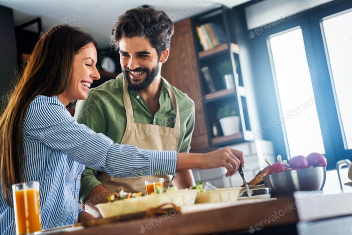 Portrait of happy couple cooking together in the kitchen at home