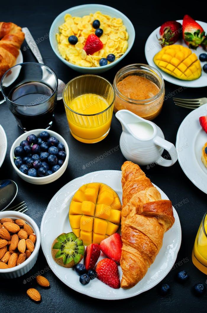 Frühstückstisch mit Flocken, Saft, Croissants, Pfannkuchen