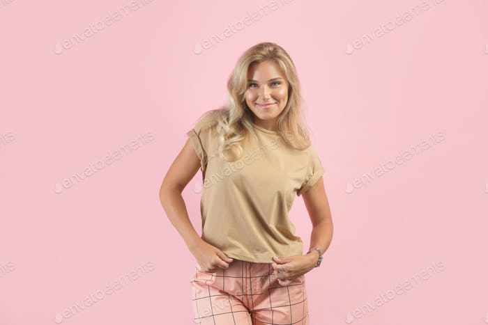 Shy young blonde woman isolated on pink background