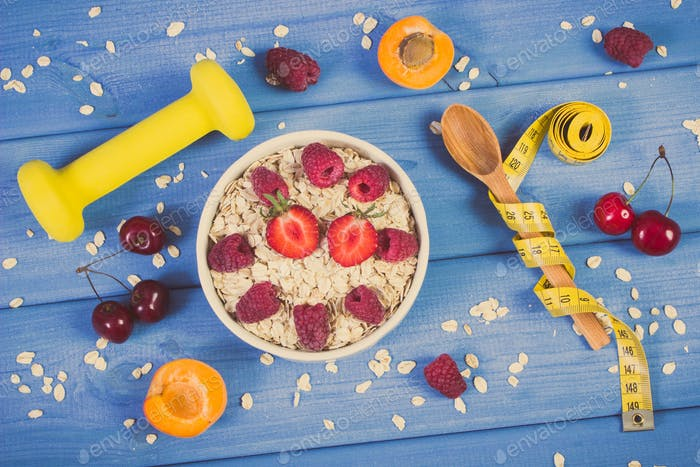 Oatmeal with fruits, tape measure and dumbbells