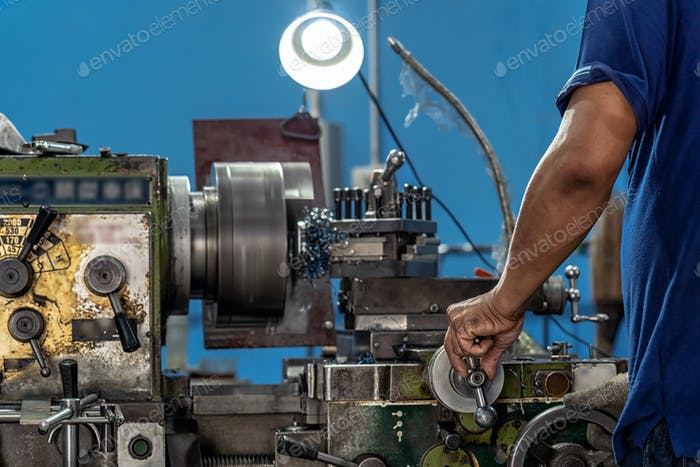 Professional machinist hand working with lathes machine in metalworking factory