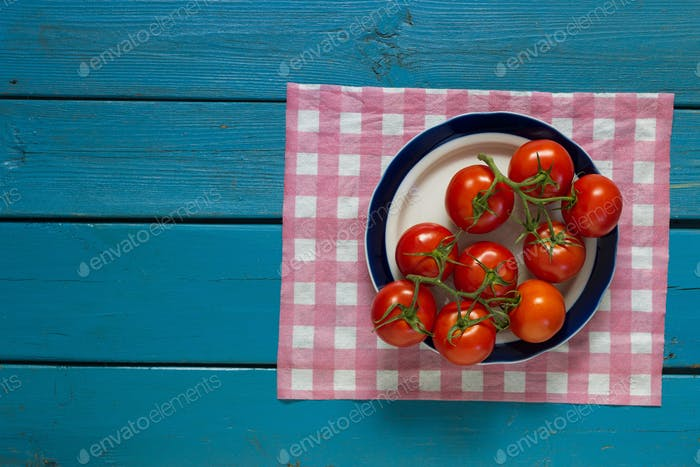 Red tomatoes lie on a plate on a blue wooden background, top vie