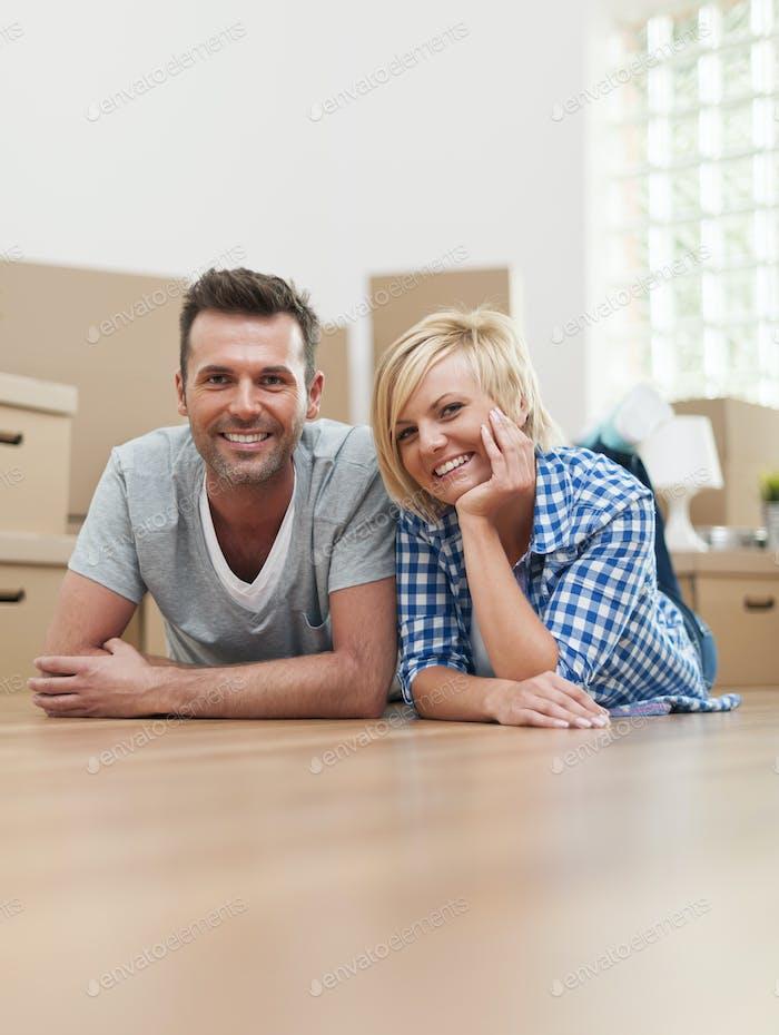 Portrait of happy couple on hardwood floor