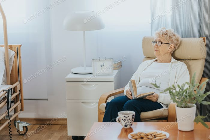 Pensive elderly lady sitting with a book in an armchair in a nursing home