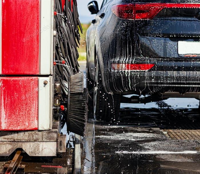 Schwarzes Auto in automatischer Waschanlage